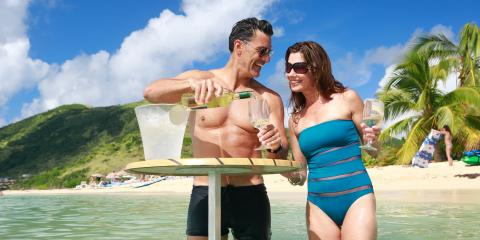 couple pouring wine on beach in St. Martin